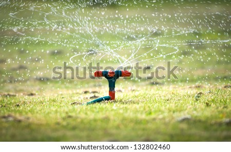 Watering system with spiral sprays going up with lots of splashes and drops falling on green grass. Device of irrigation in garden. Lawn sprinkler in close-up view. Easy gardening and agriculture. - stock photo