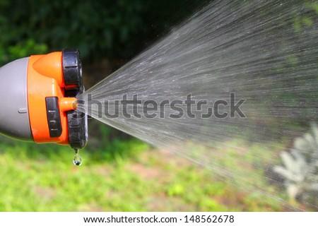 Watering the garden of universal sptay gun - stock photo