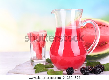 Watermelon cocktail in pitcher on wooden table on natural background - stock photo