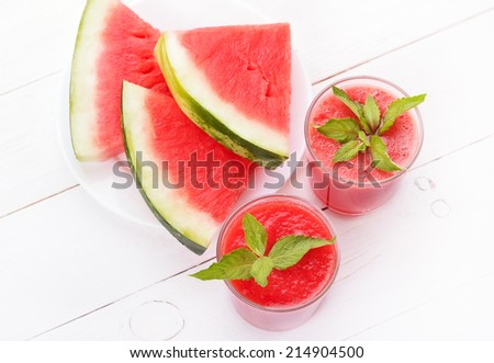 Watermelon cocktail with mint in glass and slices on white wooden table - stock photo