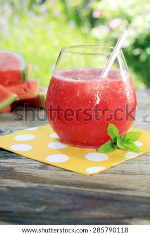 Watermelon drinks outside in the garden with straws and fresh mint.Also available in horizontal.  - stock photo