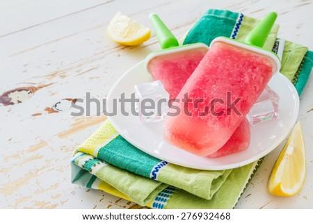 Watermelon fruit ice pops on white plate, plaid napkin, white wood background - stock photo