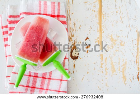 Watermelon fruit ice pops on white plate, plaid napkin, white wood background, top view - stock photo
