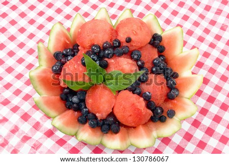 watermelon fruit salad in a decorative watermelon rind bowl served with frozen blueberries and garnished with Stevia leaves. Red and white checked plastic tablecloth for the background.