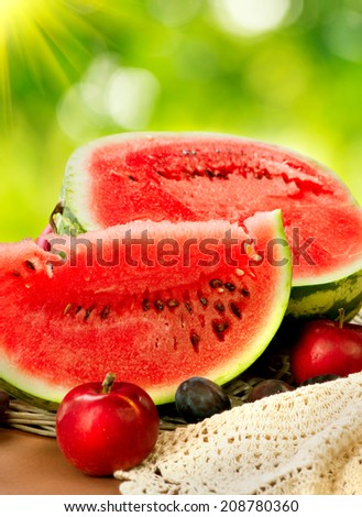 Watermelon. Juicy ripe organic watermelon slices closeup over nature green background. Autumn Fruits Still-life  - stock photo