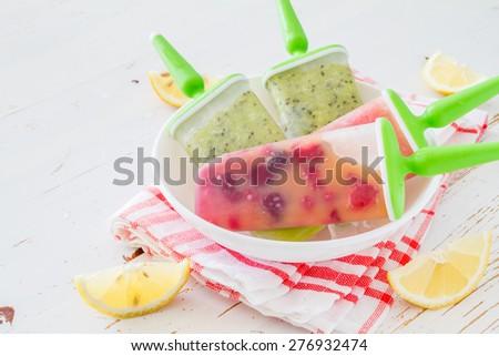 Watermelon, kiwi, berry fruit ice pops on white plate, plaid napkin, white wood background - stock photo