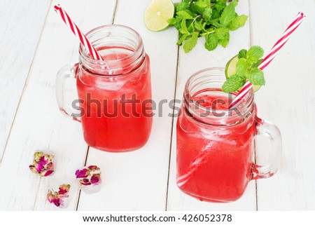 Watermelon lemonade / watermelon cocktail in mason jar with red striped straw, ice cubes with rose flowers, mint and lime on a wooden white table. Selective focus. - stock photo