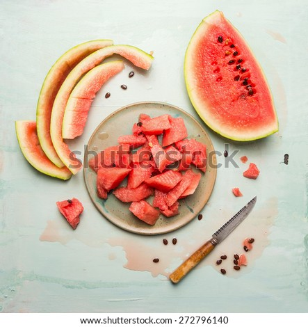 watermelon on plate with knife on blue rustic background, top view - stock photo
