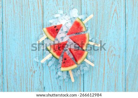 watermelon popsicle raw food yummy fresh summer fruit sweet dessert on vintage old wood teak blue flat lay - stock photo