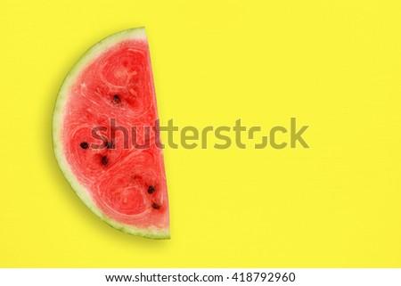 Watermelon slice on yellow table - stock photo
