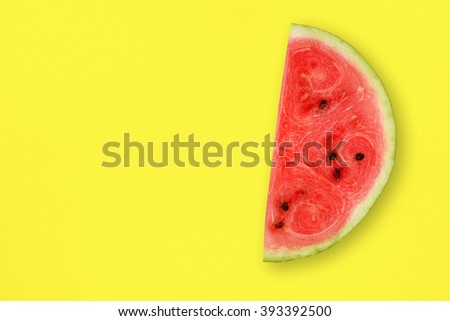 Watermelon slice on yellow table top view - stock photo