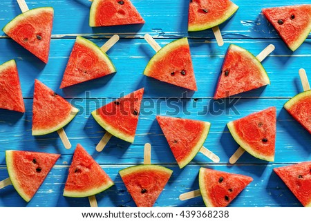 Watermelon slice popsicles on a blue rustic wood background, Popular summer fruit with yummy watermelon, Flat lay photography of Watermelon slice popsicles - stock photo
