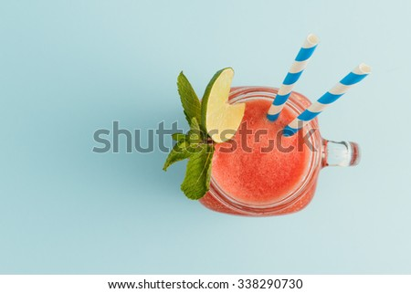 Watermelon smoothie in Mason jar with lime, mint and straws. View from above. - stock photo