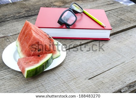 Watermelon with red book on wooden table - stock photo