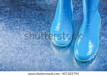Waterproof gum boots on metallic background.