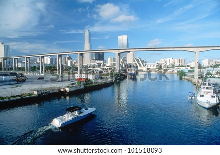 Waterway underneath metro rail line with skyline in background in Miami, Florida