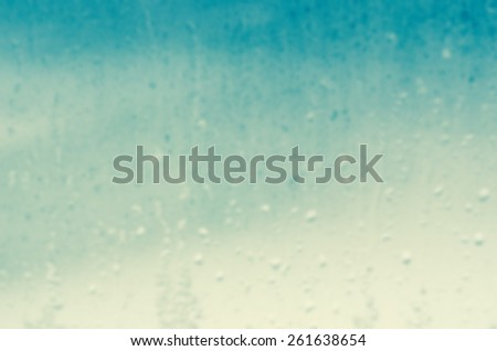 Watery background blur of  raindrops trickling down a glass window pane. - stock photo