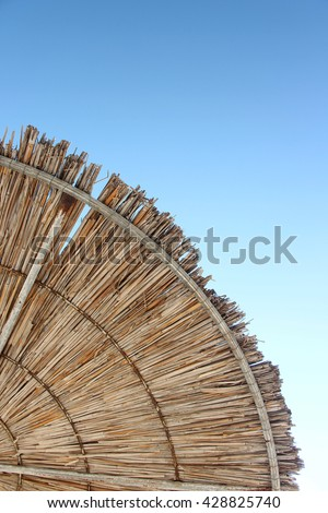 Wattled straw beach umbrella on clear blue sky background. Outdoors summertime multi colored closeup image. View from below. Vertical. - stock photo