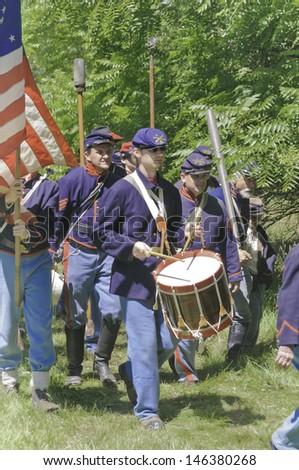 WAUCONDA, ILLINOIS/USA - JULY 13: American Civil War (1861-1865) reenactment on July 13, 2013, in Wauconda, Illinois. Union cannoneers and standard-bearer follow drummer toward a mock battle. - stock photo