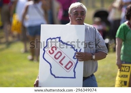 WAUKESHA, WI/USA - July 13, 2015: A man holds a protest sign in front of the convention Center where Governor Scott Walker is about to make his 2016 Presidential announcement. - stock photo