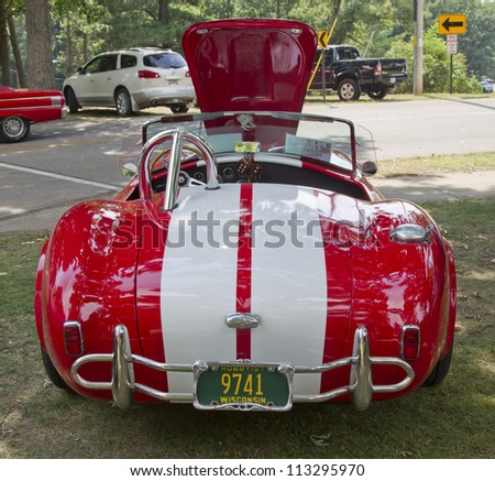 WAUPACA, WI - AUGUST 25: Back of 1965 Red White Ford AC Cobra car at the 10th Annual Waupaca Rod & Classic Car Club Car Show on August 25, 2012 in Waupaca, Wisconsin. - stock photo