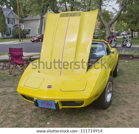 WAUPACA, WI - AUGUST 25: Bright yellow 1975 Chevy Corvette Stingray classic car at the 10th Annual Waupaca Rod & Classic Car Club Car Show on August 25, 2012 in Waupaca, Wisconsin. - stock photo
