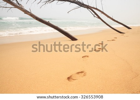 Wave and footsteps - stock photo