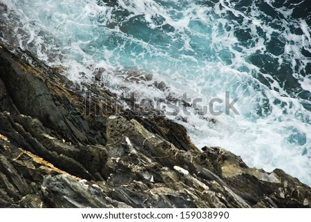 Wave breaking against cliff in Cinque Terre, Italy, view from above - stock photo