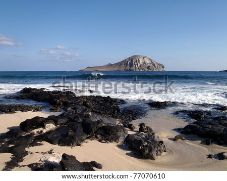 Wave crashing at rocky Baby Makapuu beach with Rabbit Island in the Distance - stock photo