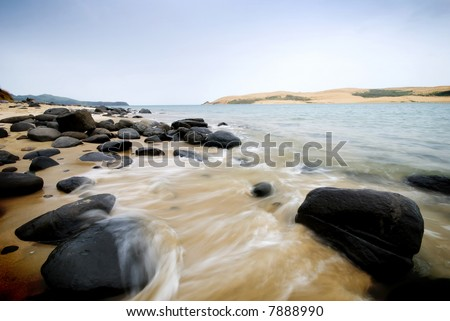 Wave crashing in on beautiful coastline - stock photo