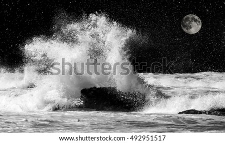 Wave crashing over rock with moon behind