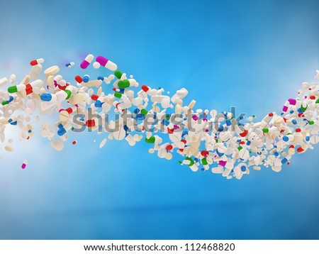 Wave from Colorful Medical Pills on blue background - stock photo