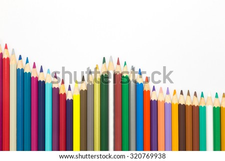 Wave of multiple wooden colour pencils on white background  - stock photo