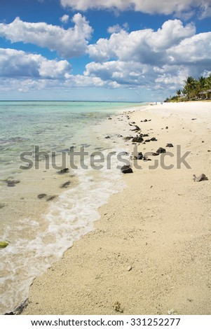 Wave of the ocean on the sand beach in Mauritius. Blue sky on background. Mauritius island. Selective focus.