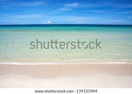 Wave of the sea on the sand beach against blue sky - stock photo