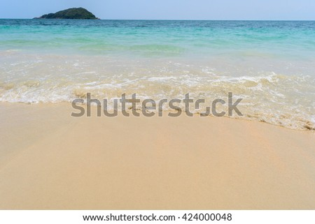 Wave of the sea on the sand beach with island background