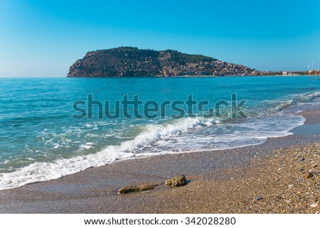 Wave on the beach and beautiful view to ancient fortress on the Alanya peninsula Turkey. Toned.
