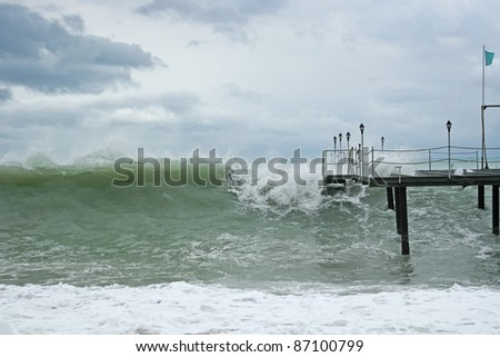 wave over pier - stock photo