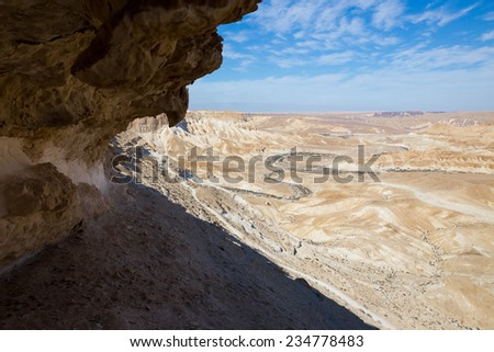 Wave shaped cliff mountain crag above dry river bed, Negev mountains, Israel.