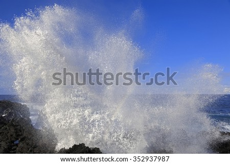 Wave splash with rainbow on the rocks, Azores, Portugal