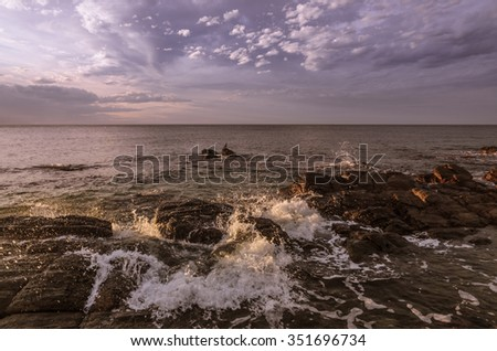Wave splashes boulder rocks seascape at sunset - stock photo