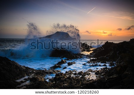 Wave spray at sunset by Worms Head in Wales - stock photo