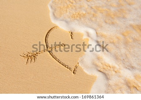 Wave washes over heart in the sand - stock photo