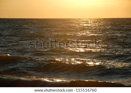 Waves and rays of a sun are reflected in the sea