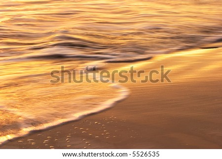 Waves and water flowing over sand at sunset in Santa Barbara. - stock photo