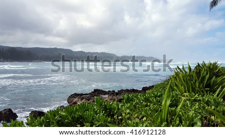 Waves Break as they roll towards shore with Coral Rock and trees on the North Shore of Oahu, Hawaii. - stock photo