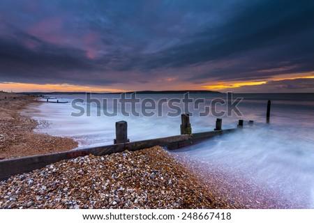 Waves break on a shingle beach overlooking the Isle of Wight - stock photo
