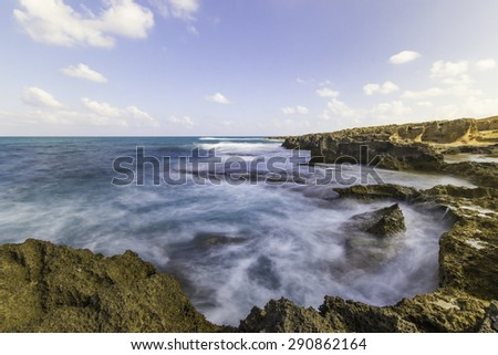 Waves breaking of a rocky beach. The water look like milk due to the use of natural density filter - ND. The background is blue sky and white clouds.