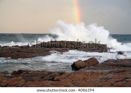 waves breaking on a Rocky beach with rainbow over the ocean - stock photo