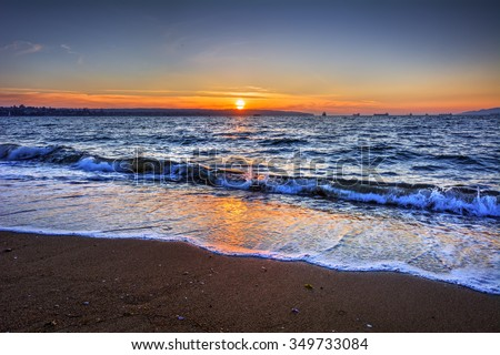 Waves breaking on the beach, orange sunset, and ships on the horizon - stock photo